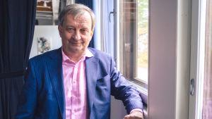 Hjallis står med rosa skojrta och marinblå kostym vid ett fönster.
