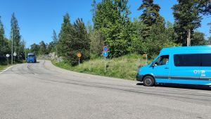 En buss står parkerad på en väg och en lastbil kommer körandes emot.