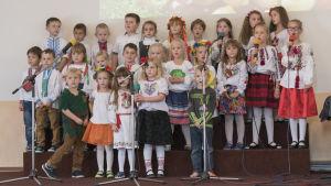 En grupp med barn står på en scen och sjunger.