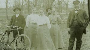 Gruppbild med fem ungdomar och en äldre man utomhus. Ung man med cykel och cigarett i munnen.