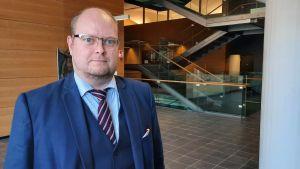 Skallig man med glasögon blå kostym och slips.