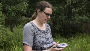 en kvinna med brunt långt hår och blå skjorta med brodering.