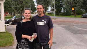 en kvinna och en man som står bredvid varandra. I bakgrunden en parkering och träd