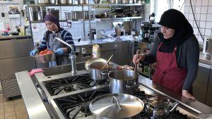 I ett storkök rör en kvinna med svart huvudduk i en kastrull på spisen och en annan kvinna håller en skål med tomater.