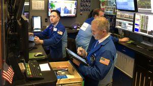 Börsmäklare vid sina bildskärmar i New York aktiebörs.