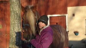 Jeanne-Marie Törnroth med sin häst Pilsner utanför sitt stall i Pikis