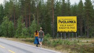 Nainen ja mies kävelevät maantien reunaa pitkin suuren, keltaisen kyltin ohi.