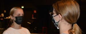 Desirée Kavander, en ung flicka med vit t-skjorta, hästsvans och svart munskydd stirrar en annan flicka rakt in i ögonen på en mörk teaterscen.