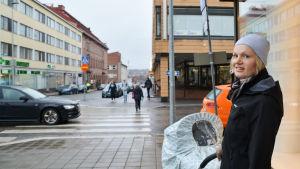 kvinna med bebis står vid hörnet av Lundagatan och Biskopsgatan i Borgå en grå dag i november