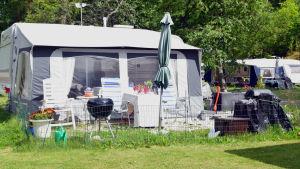 Husvagn med bord, grill,s taket och andra grejer framför.