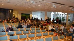 Mänskor som sitter i ett auditorium.