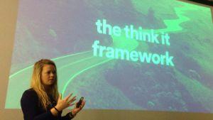 """Sofie Lindblom står framför en stor skärm på väggen, där det står """"the think it framework"""""""