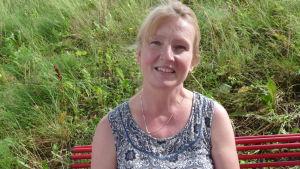 profilbild på Camilla Lundqvist. Hon sitter på en röd parkbänk. Bakom frodigt grönt gräs.