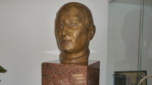 Byst i brons, föreställer ett huvud på Axel A Dahlström som har testamenterat sin förmögenhet till Bromarfhemmet.
