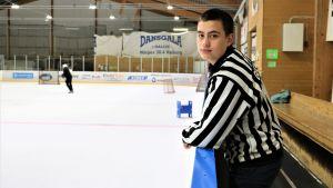 Isak Gull är ishockeydomare för yngre lag. Han står i domarskjorta utanför isen i Närpes ishall.