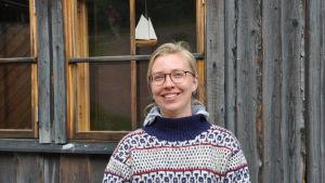 Närbild på Daniela Grotenfelt som står invid båtmuseet i blåvitmönstrad ylletröja.