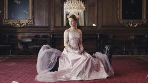 Alma (Vicky Krieps) sitter i en ljudsröd sidenklänning och poserar under en kristallkrona.