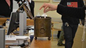 En hand lägger en valsedel i en urna.