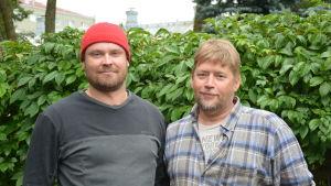 Jarno Sula och Petri Vahteri står utomhus framför en grön häck och tittar in i kameran.