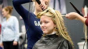 En blond kvinna får sitt hår lockat av två frisörstuderande.