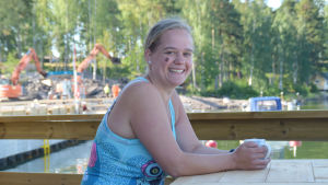Ragna-Lise Karlsson sitter med en kaffekopp i händerna vid en uteservering. I bakgrunden skymtar en småbåtshamn.