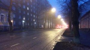 Röda baklyktor syns på bilar som kör längs en dimmig, regnig gata i en stad.