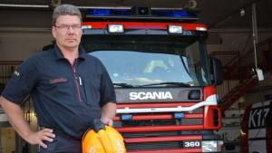 Sture Holmström med en orange hjälm i handen framför en brandbil.
