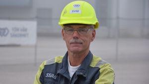 en man i blågula verkstadskläder,  och gul skyddshjälm. Utomhus, dimma, man kan skönja fabriksbyggnad i bakgrunden.