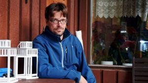 Thomas Grönberg sitter på en altan i en blå rock. Han tittar in i kameran.