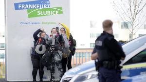 Tre damer tar en selfie vid gränsen Slubice-Frankfurt (på den tyska sidan) bredvid de långa bilköerna.