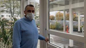 Man i ljusblå tröja och vitt munskydd öppnar dörren från inglasat uterum till trädgård utanför.