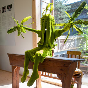 Ett konstverk av keramikern Kim Simonsson föreställer ett grönt barn med fjädrar i händerna.