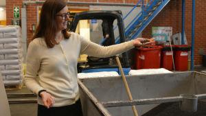 Kvinna i vit tröja håller plastpelletar från ett kärl på en fabrik i handen.