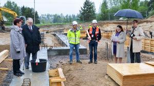 Politiker, byggare och kyrkoherdar står på en regning byggplats, i mitten trälåda där grundstenen muras in