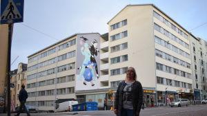 En kvinna står på gatan framför en husgavel med en muralmålning (väggmålning).