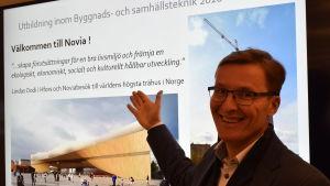 Mats Lindholm visar bilder som relaterar til byggundervisningen på Novia.