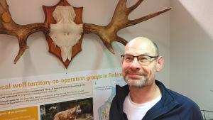 Jörgen Hermansson, en man med glasögon, står vid en vägg under ett stort älg.