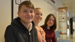 Ungdomar sitter på en bänk i skolans korridor.