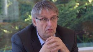 En allvarlig man sitter med löst knäppta händer framför sig. Sjundeås kommundirektör Juha-Pekka Istupa
