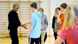 Marco Dias lär skolelever självförsvar i en gympasal.