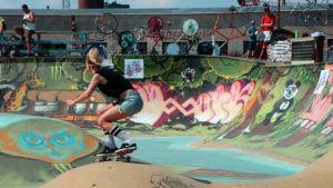 En ung kvinna åker rullbräda i en rullbrädspark (skatepark).
