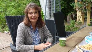 Riikka Slunga-Poutsalo på sin terass med en kaffekopp framför sig.