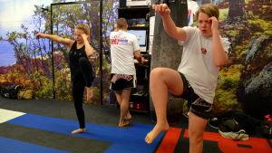 En kvinna och en man som tränar thaiboxning.