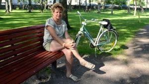 En kvinna sitter på en röd parkbänk bredvid en cykel.