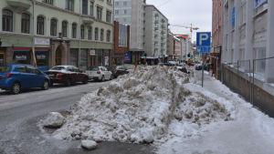 Stor snöhög i parkeringsruta på Köpmansgatan i Åbo centrum.