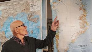 Mies osoittaa sormellaan Grönlannin karttaa