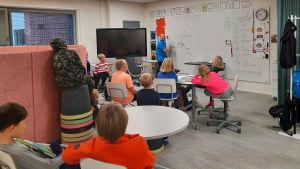 Elever sitter och lyssnar på lärare som ritar på tavlan.
