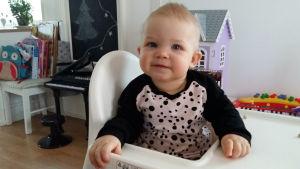 Litet barn sitter i matstol iklädd kläder som mamma har sytt