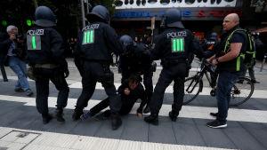 Polisen griper en demonstrant i Chemnitz.