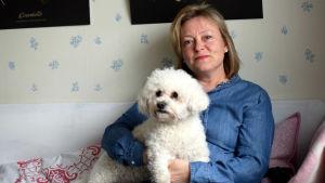 Tina Landén sitter i en träsoffa med hunden Knut i famnen.